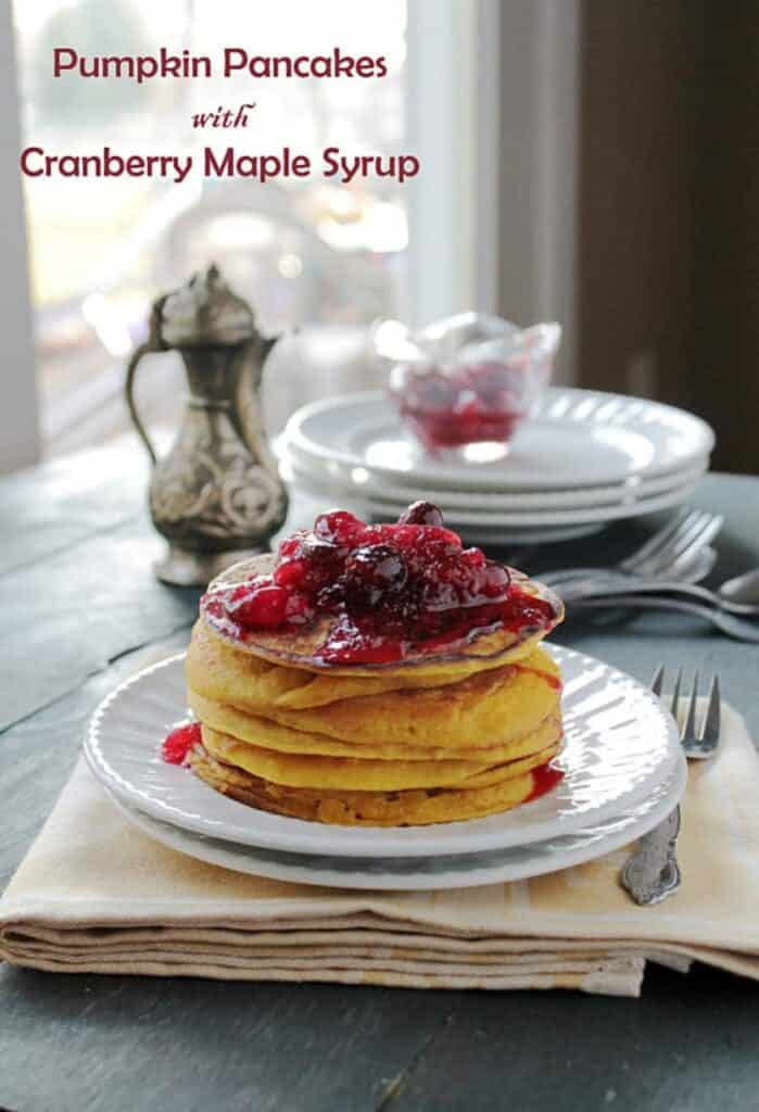 A plate of golden-brown pumpkin pancakes topped with cranberry maple syrup.