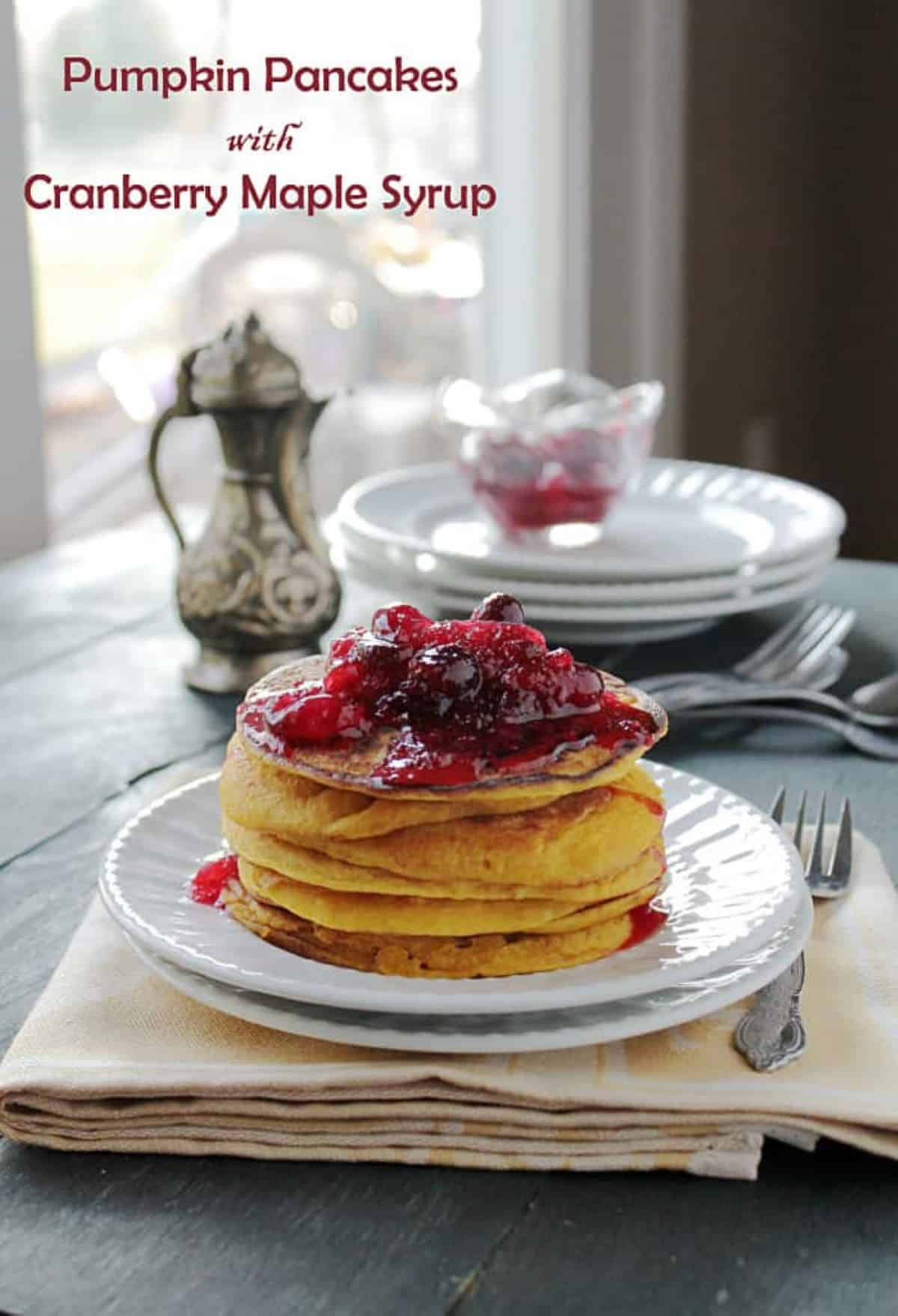 A plate of golden pancakes topped with cranberry syrup and fresh cranberry sauce.