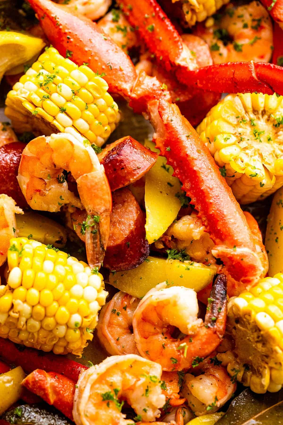 up close shot of seafood boil with crab legs, shrimp, corn, potatoes, and sausages