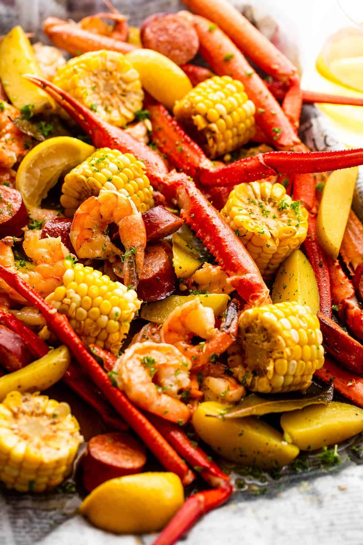 crab legs, shrimp, and corn served on a baking sheet