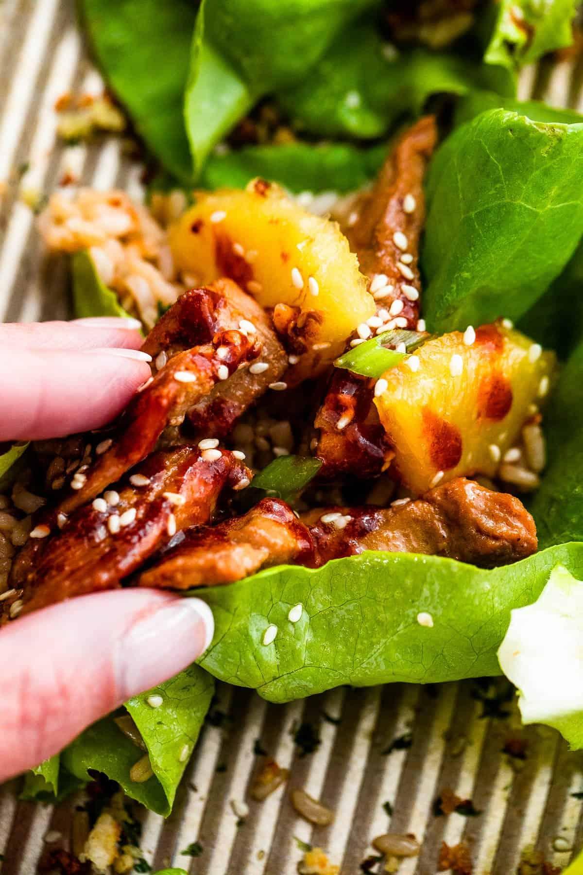 a hand grabbing a pork lettuce wrap