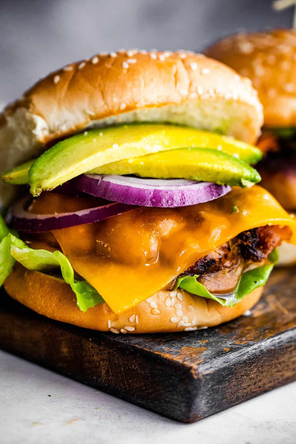 turkey burger with cheese, avocado, and a slice of red onion, set in between sesame seed buns