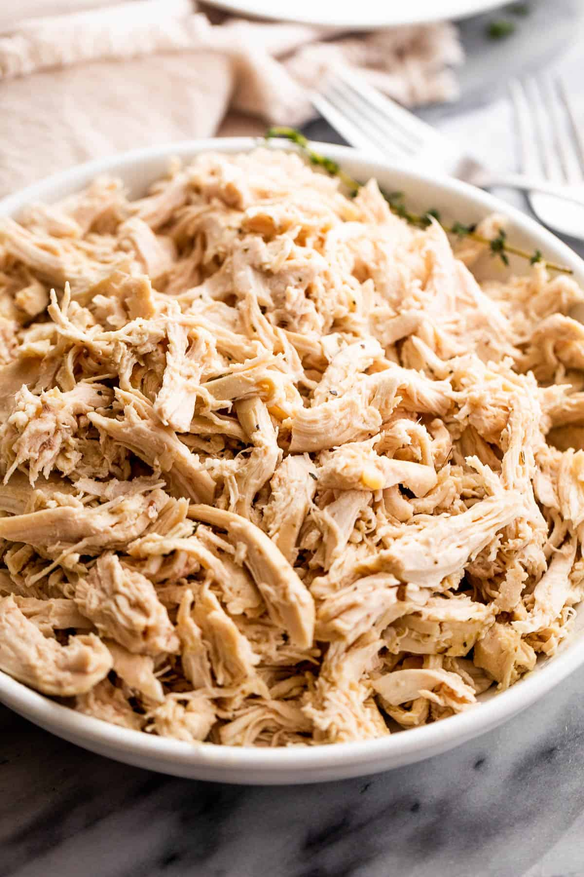 shredded boiled chicken breasts in a white serving bowl