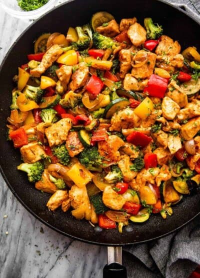 overhead shot of cut up chicken breast cooked in a skillet with zucchini, broccoli, and bell peppers