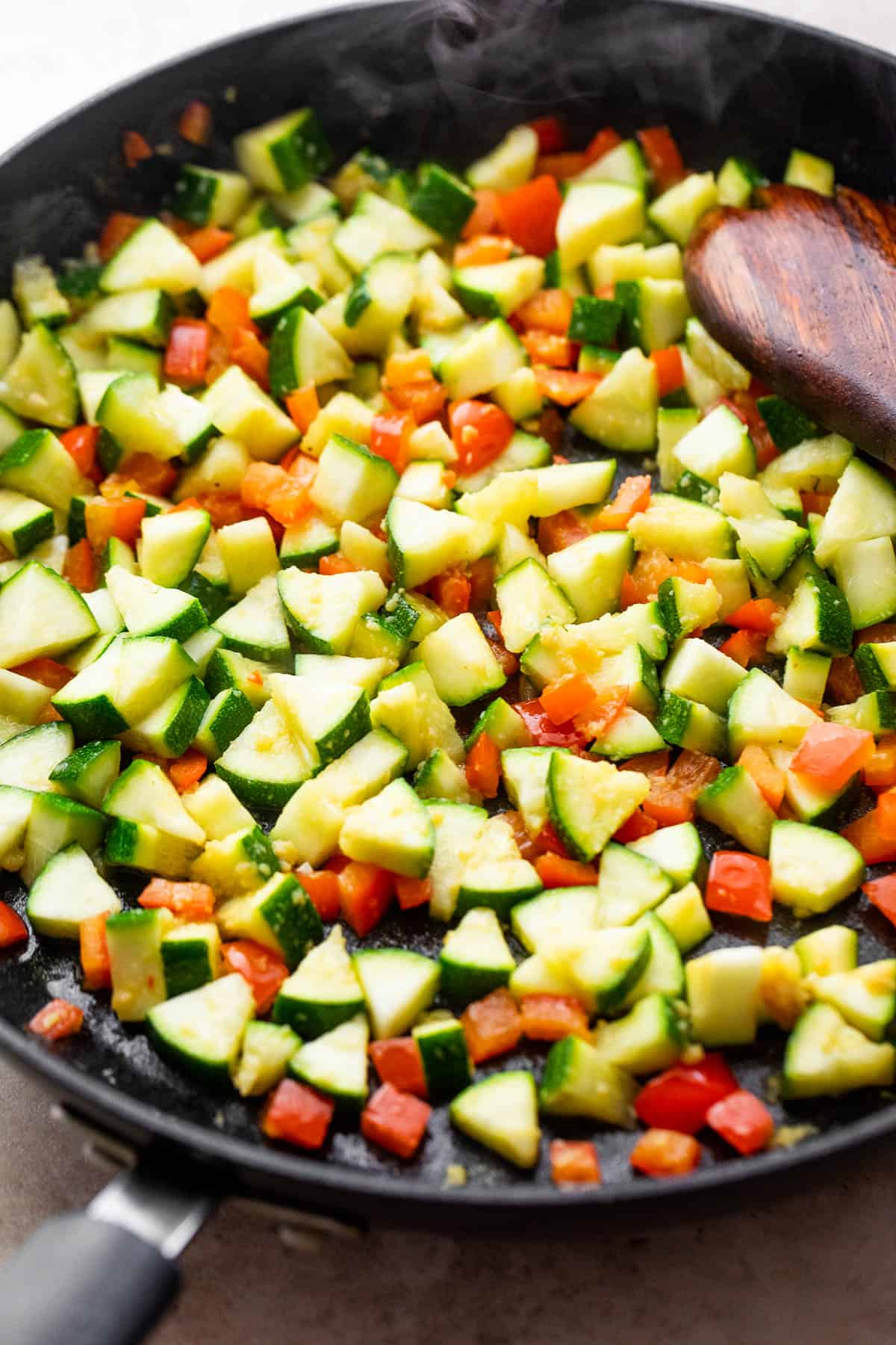 diced zucchini and diced red bell pepper cooking in a black skillet