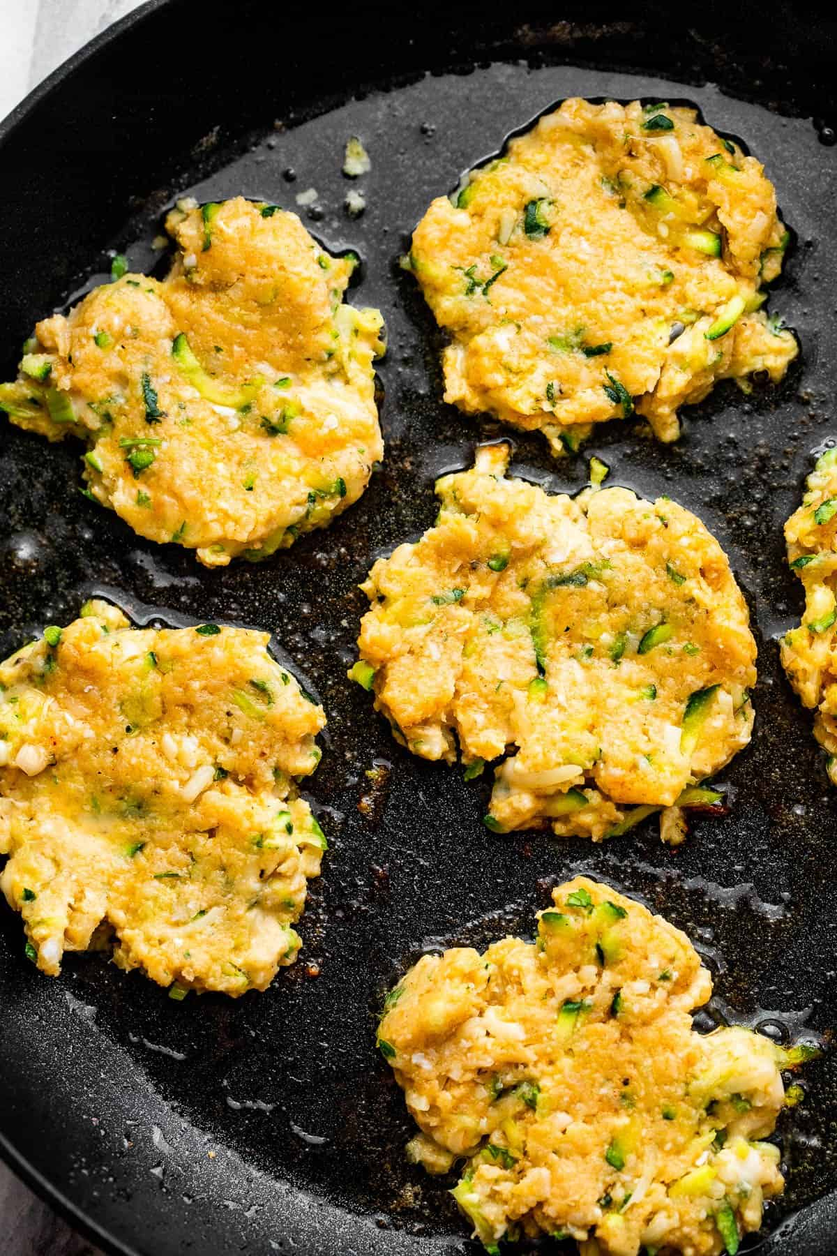 cooking zucchini chicken fritters in a black skillet