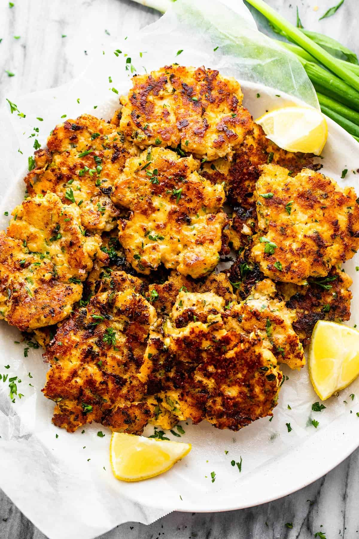 zucchini chicken fritters served on a plate with lemon wedges and green onions to the side.