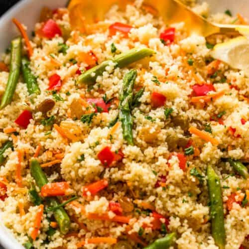 couscous served in a white bowl and garnished with asparagus pieces, shredded carrots, raisins, and diced red bell pepper