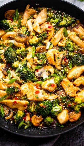 preparing hunan chicken in a black skillet