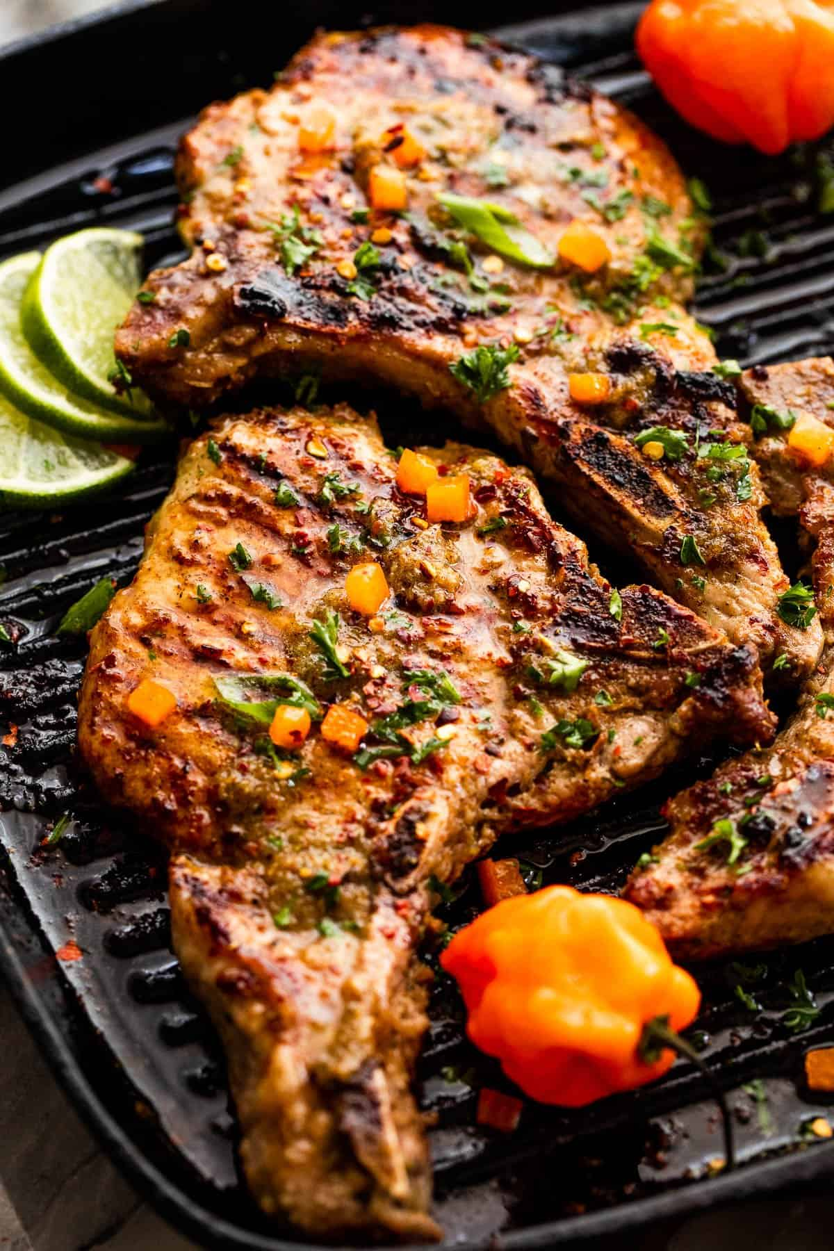 side shot of grilled jerk sauce pork chops in a grill pan with habanero peppers and lime slices to the side