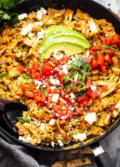 Migas in a skillet topped with sliced avocados, diced tomatoes, and cotija cheese
