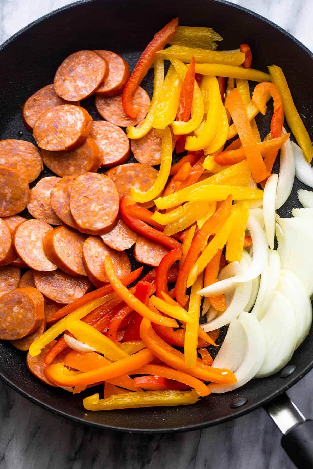 szeletelt hagymát, paprikát és andouille kolbászt fekete serpenyőbe rendezve