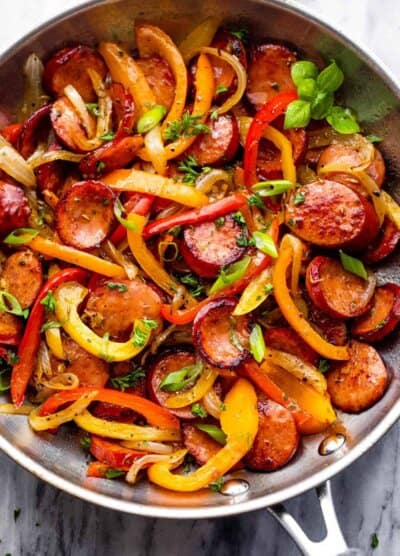 stainless steel skillet with cooked sliced peppers, sausages, and onions