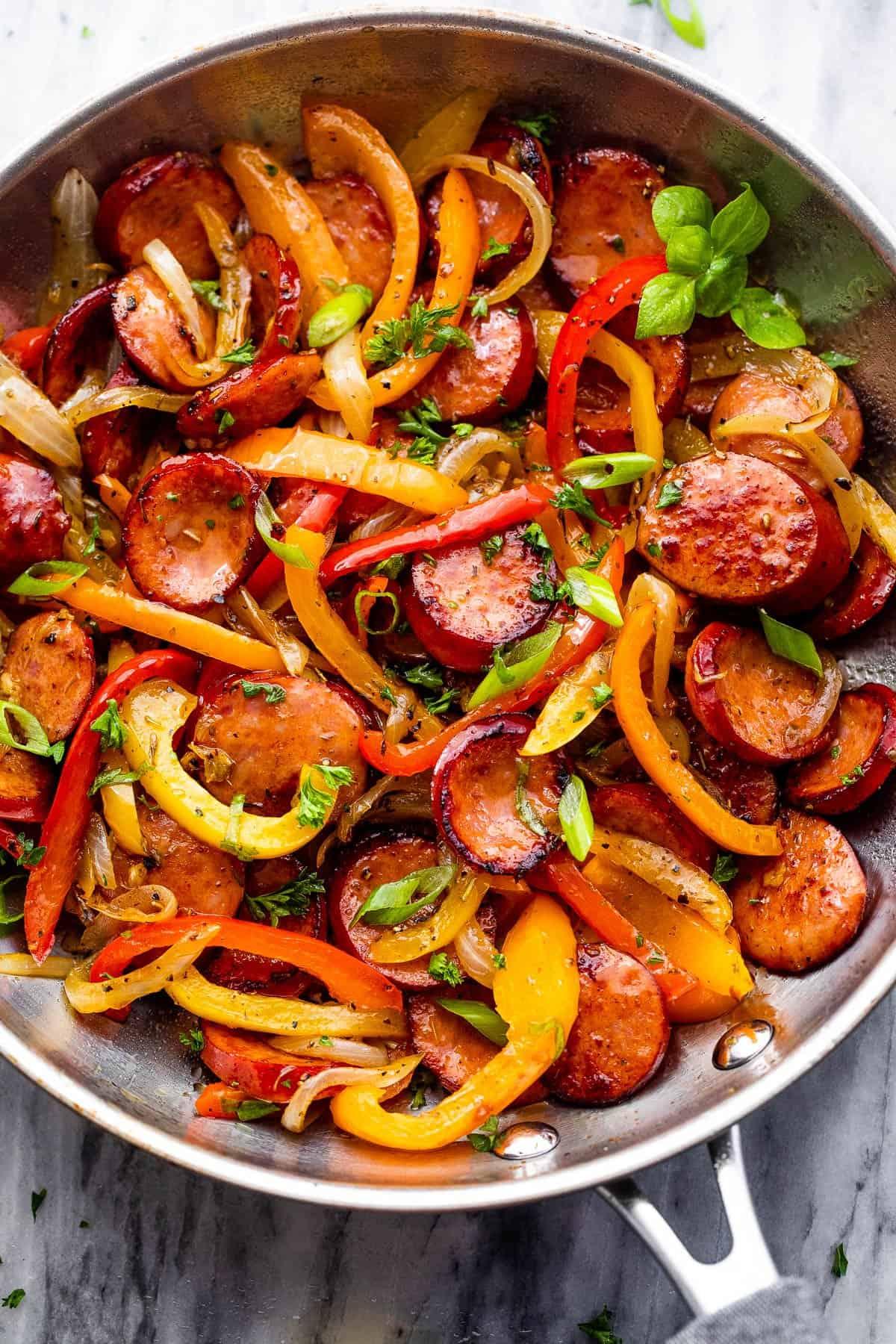 rozsdamentes acél serpenyő főtt szeletelt paprikával, kolbásszal és hagymával