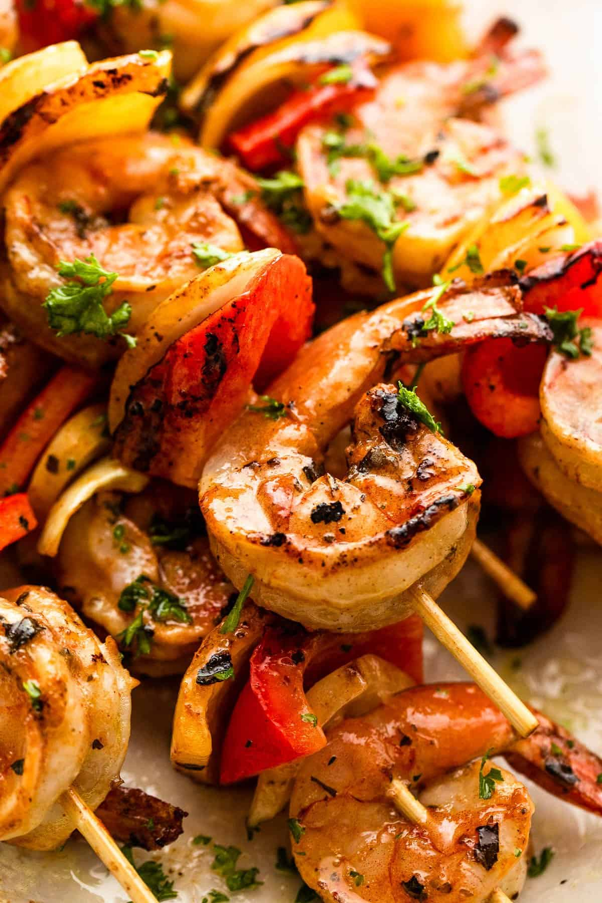 up close photo of shrimp and peppers on skewers