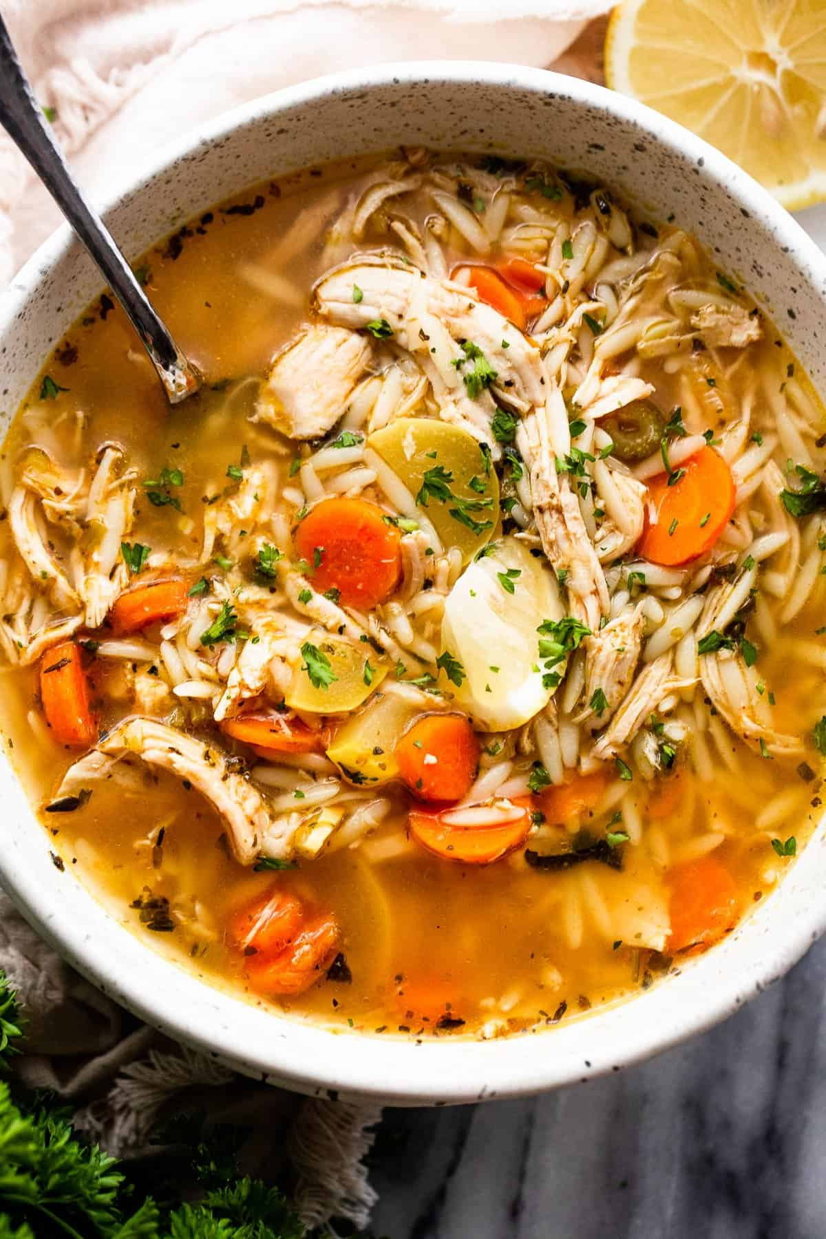 chicken orzo soup served in a white soup bowl with a spoon