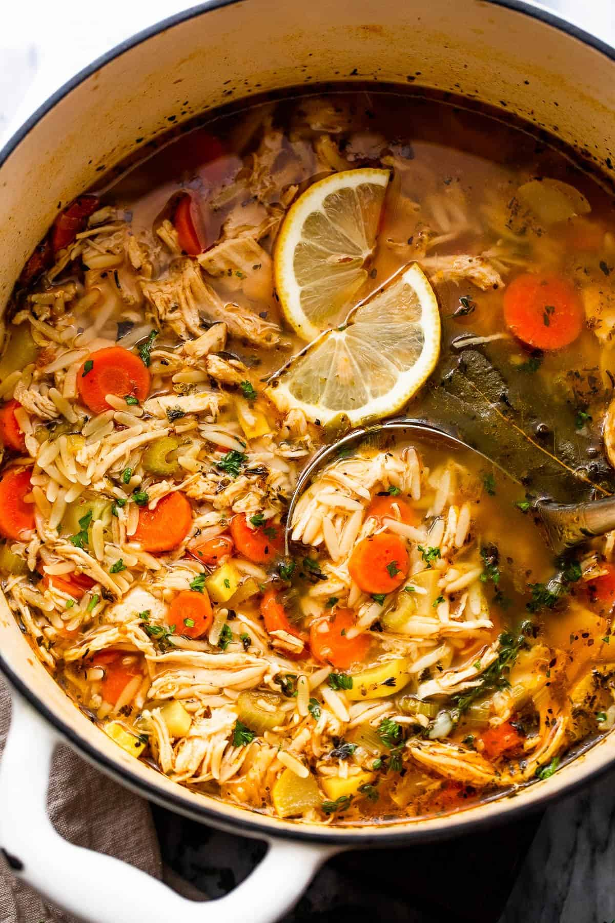 overhead shot of chicken orzo soup in a dutch oven