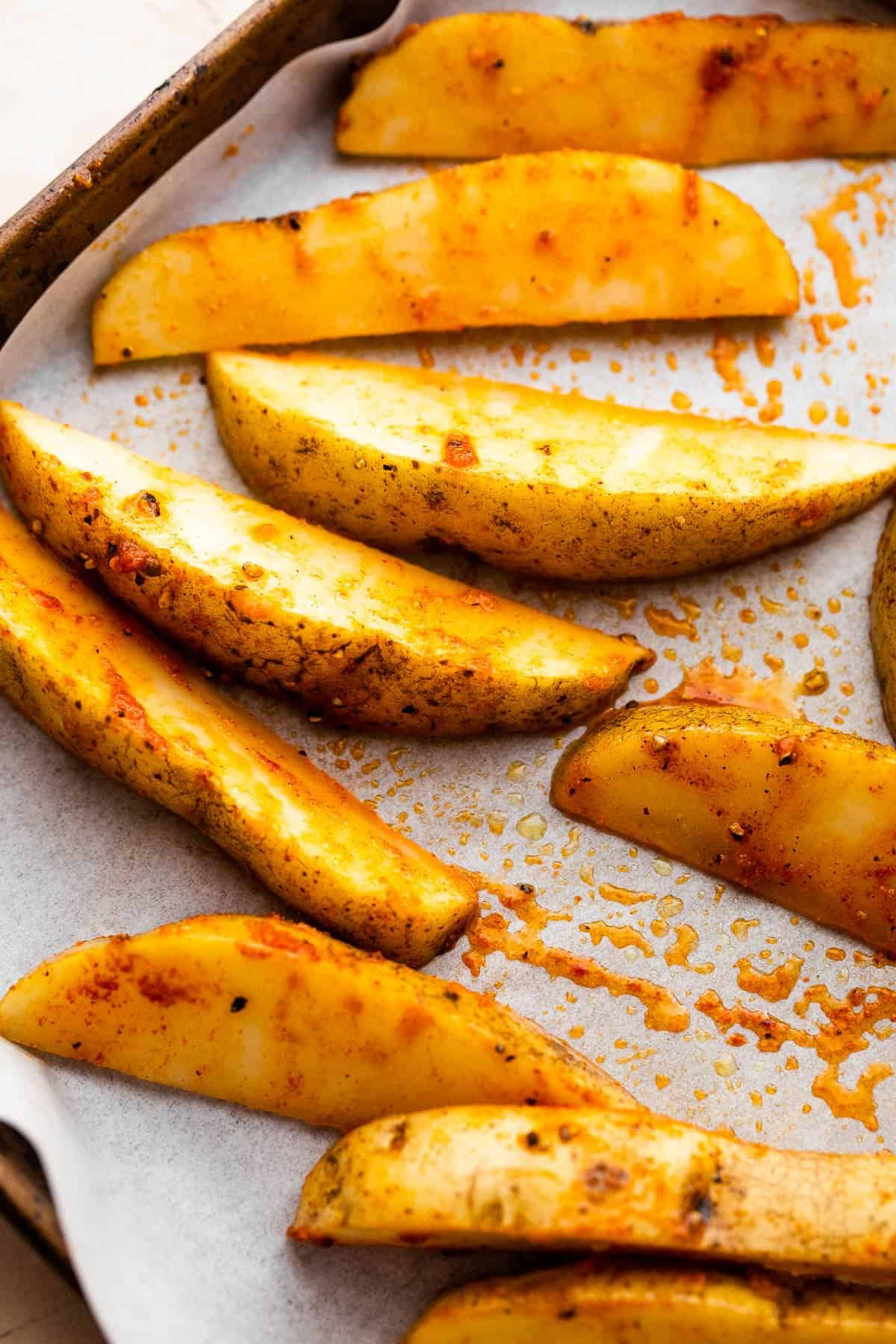 raw and seasoned russet potato wedges arranged on a sheet pan covered with parchment paper