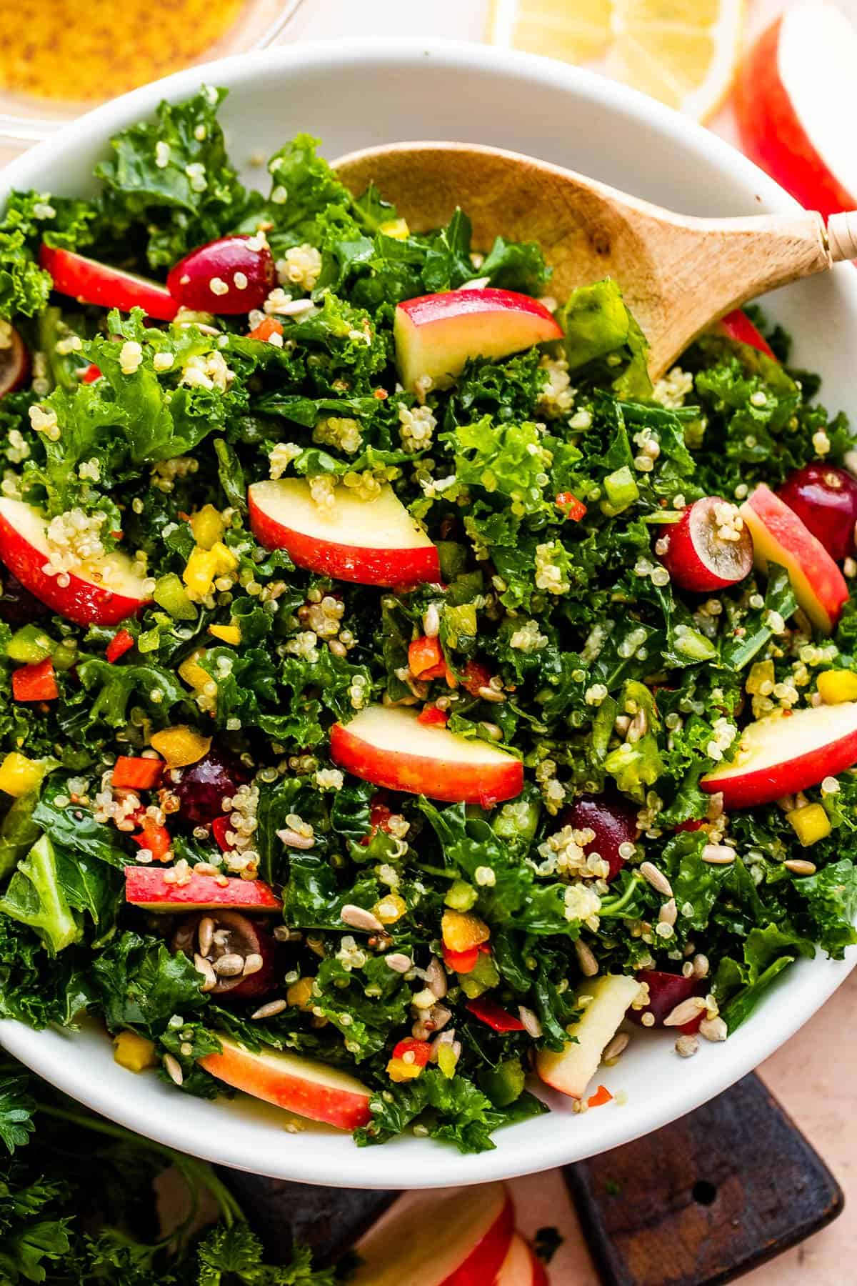 close up overhead shot of Crunchy Kale Quinoa Salad studded with apple slices, halved grapes, sunflower seeds, and bell peppers.