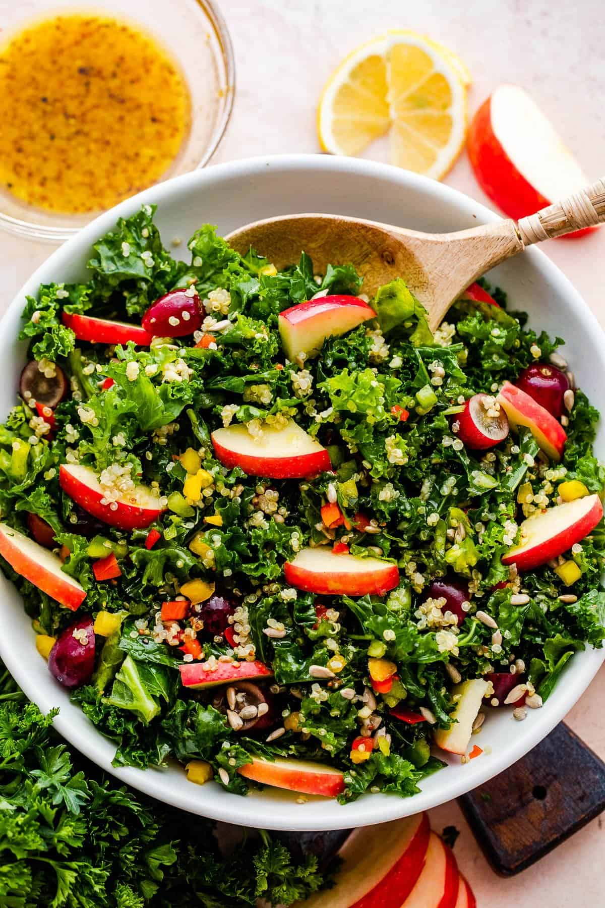 Crunchy Kale Quinoa Salad in a white bowl with a wooden spoon inside the bowl.