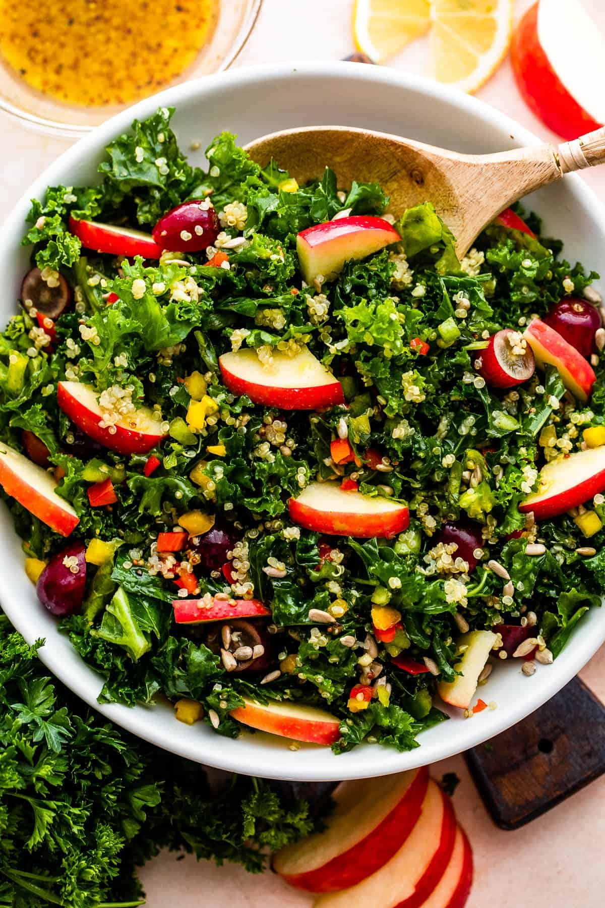 overhead shot of Crunchy Kale Quinoa Salad with slices of apples and lemons arranged around the salad.