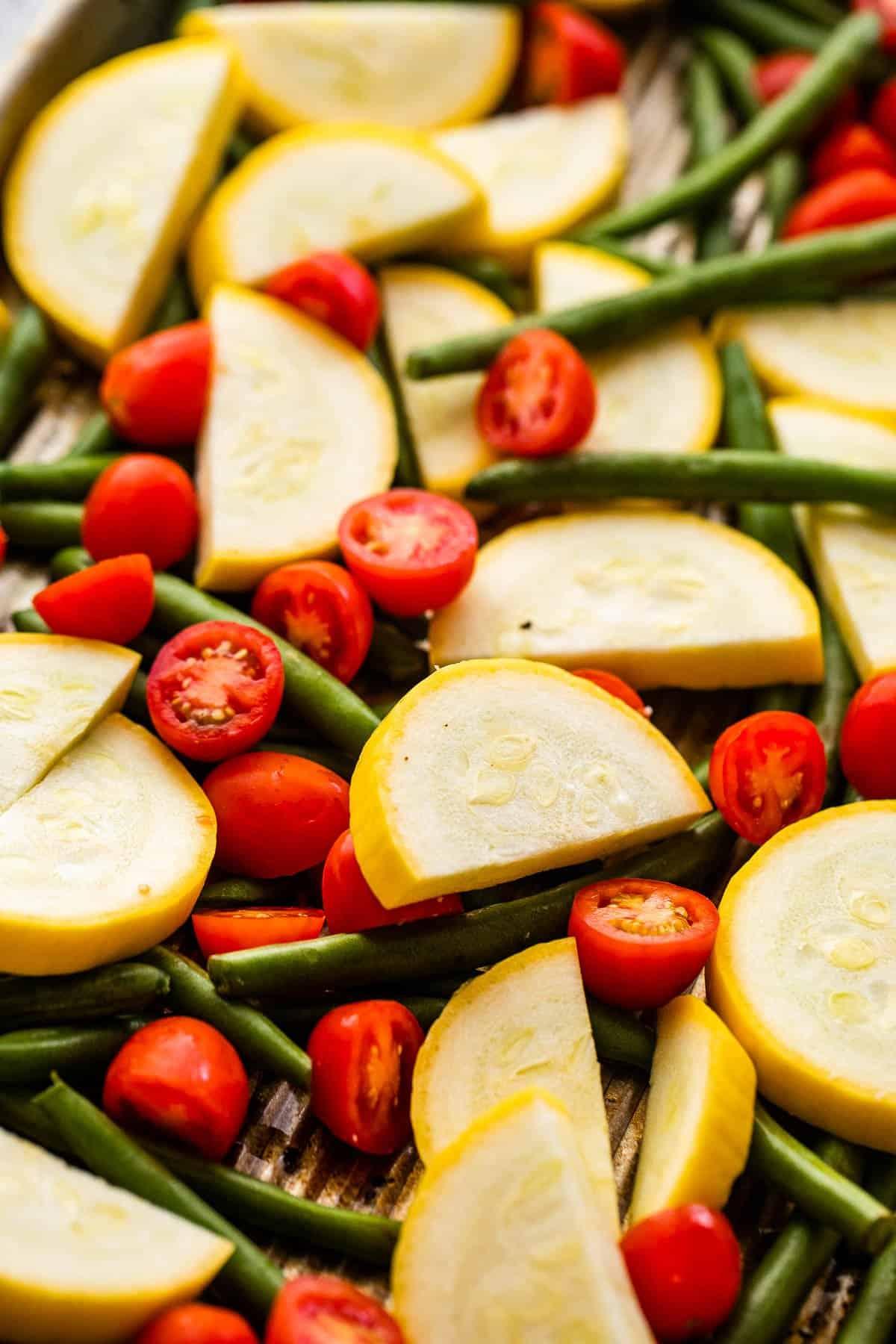 közelről készített fotók félbevágott cseresznyeparadicsomról, felezett sárga cukkiniről és egész zöldbabról