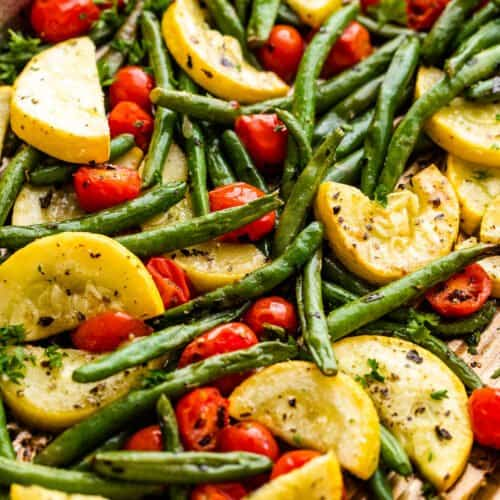 halved cherry tomatoes, halved yellow squash, and whole green beans on a sheet pan