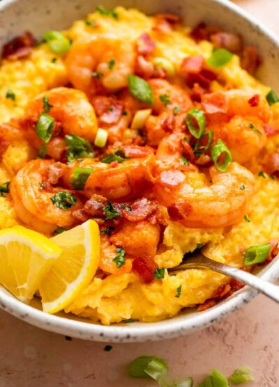 side view of a bowl with slow cooker grits topped with shrimp, bacon, and green onions