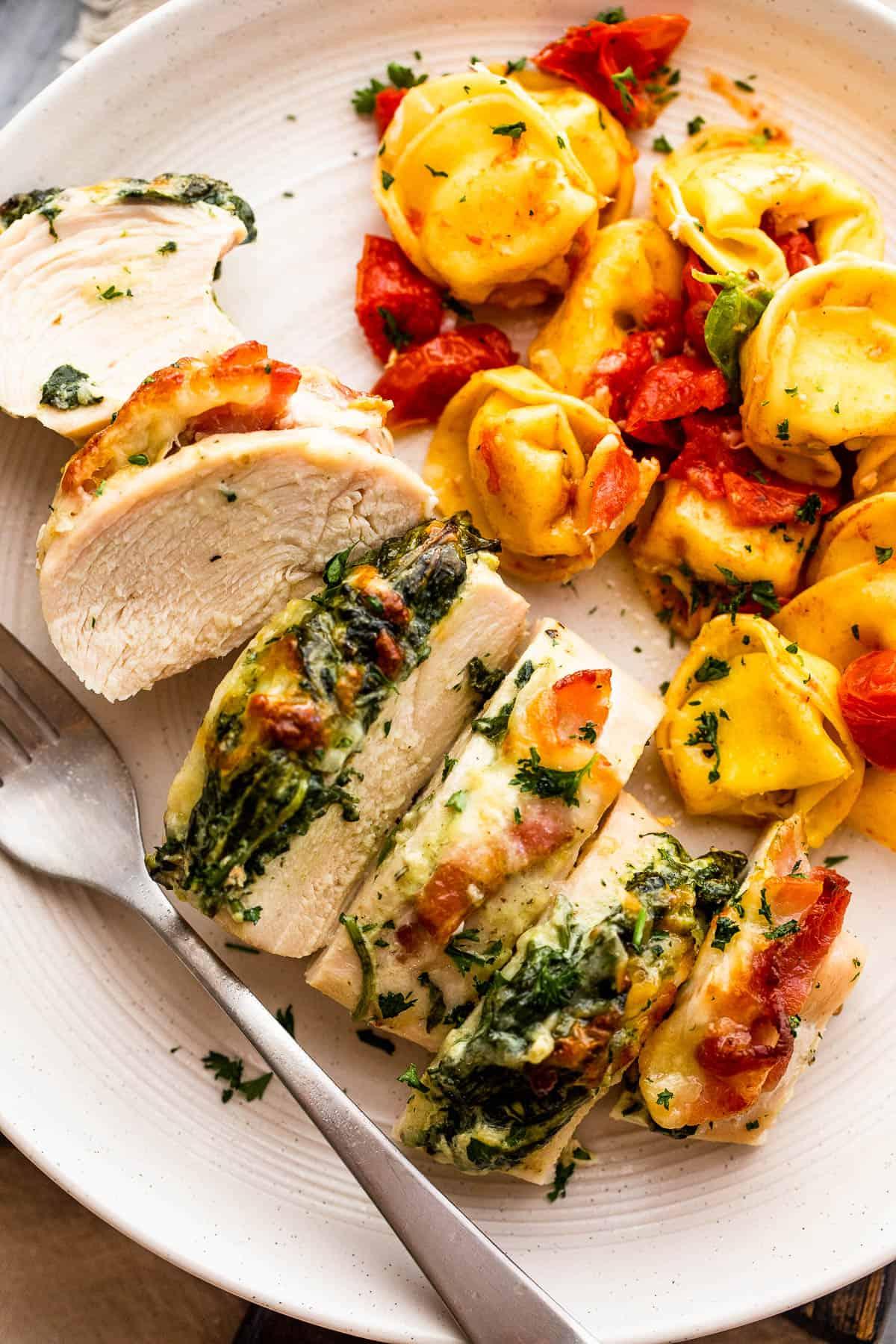 Tányér spenóttal töltött csirkemellel és szalonnával, tortellini tésztával tálalva