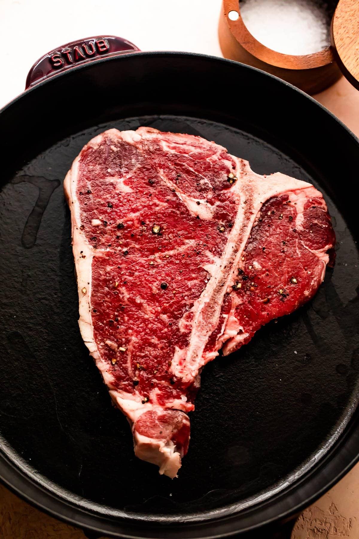 raw t-bone steak in a skillet