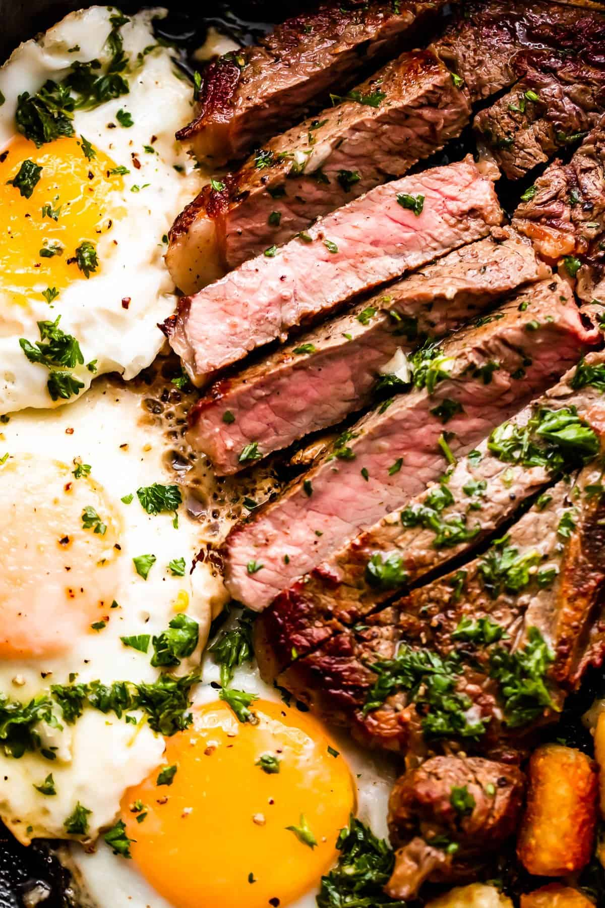 close up shot of t-bone steak cut in slices and served next to three eggs cooked over easy .