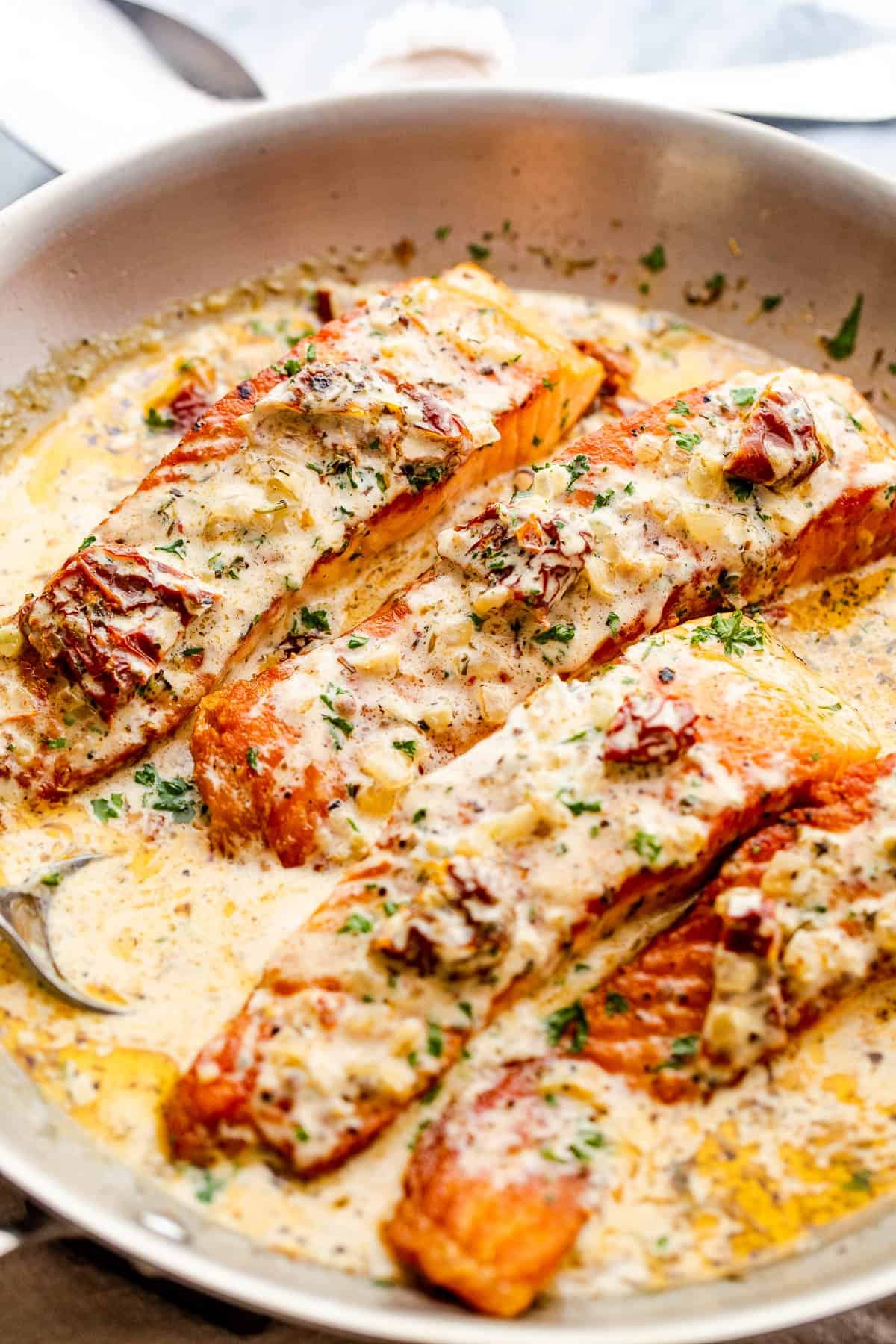 four salmon fillets in a skillet with cream sauce