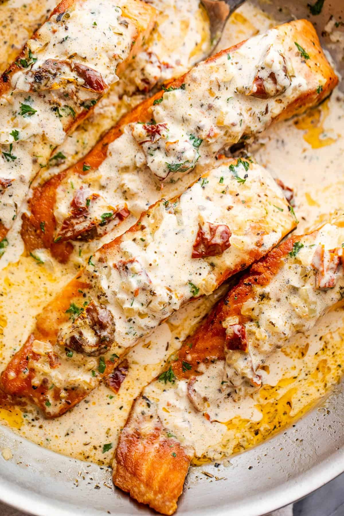 overhead shot of four salmon fillets in a skillet with cream sauce