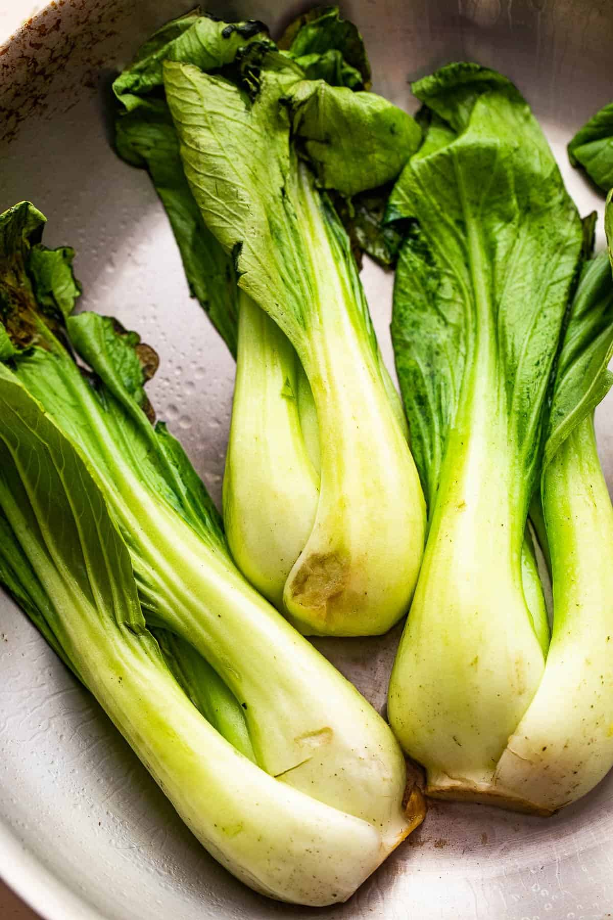 raw bok choy in a stainless steel skillet